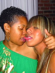 Young African American high school girls kissing in front of the camera