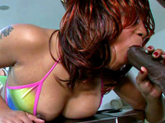 Red haired ebony Patty Kake lying on the table and sucks huge black dick
