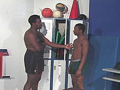 Two black guys are hanging out in the locker room after gym class. However, the large guy drops to his knees..