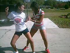 Two perky black teens indulge in the street